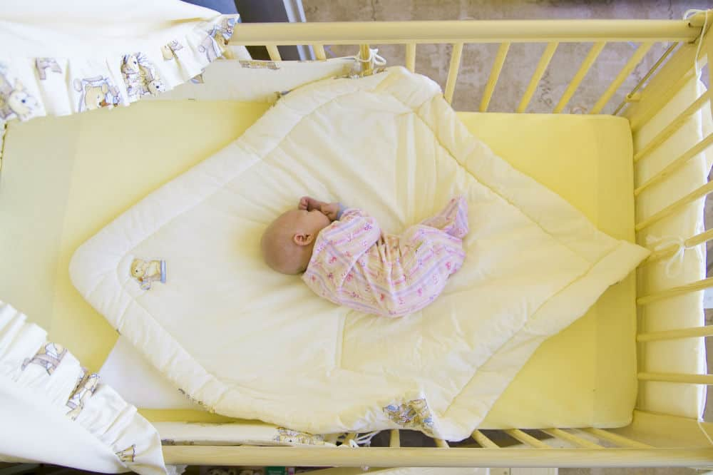 When can you put a blanket in a baby crib